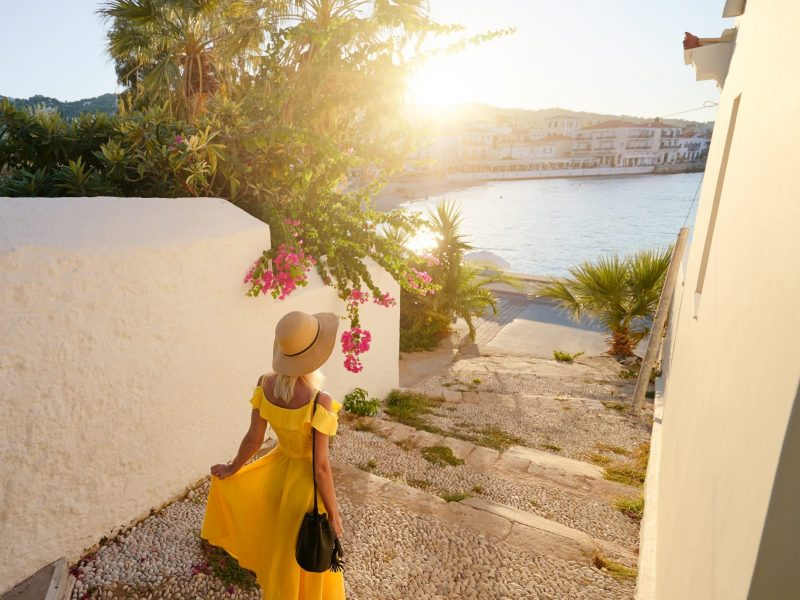 Young traveling woman in hat and yellow dress walking on old town enjoying the sea view.